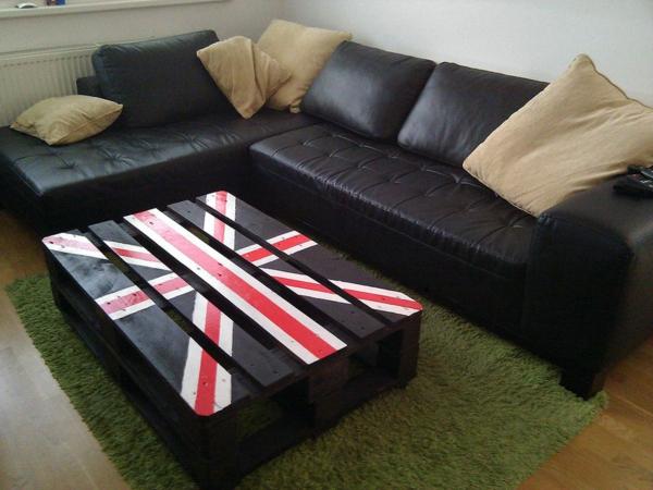 moderner-und-super-aussehender-europaletten-tisch-neben-einem-schwarzen-sofa