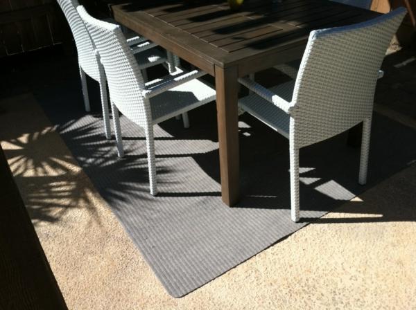 weiße-stühle-massiver-tisch-outdoor-teppich-in-grau
