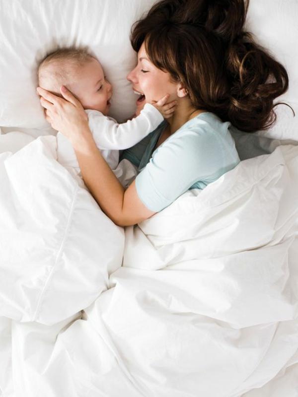 baby-und-familie-mutter-und-kind-haben-spaß-im-bett