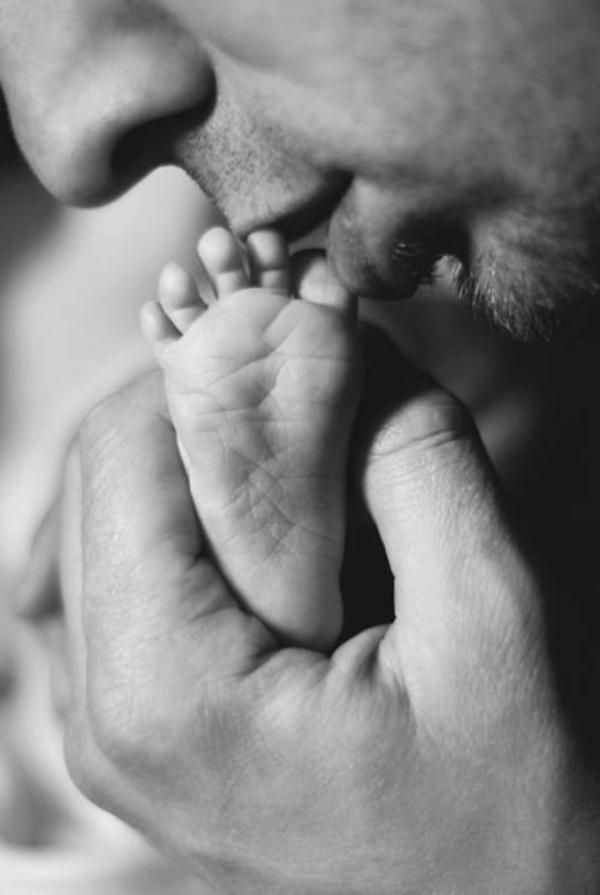 baby-und-familie-vater-küsst-den-fuß-des-babys