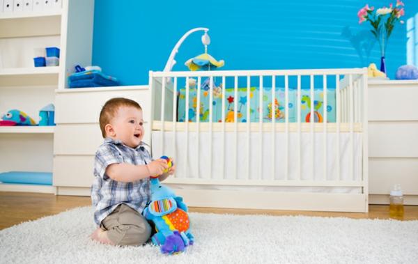 babyzimmer-junge-süßes-baby-auf-dem-boden-weißes-babybett