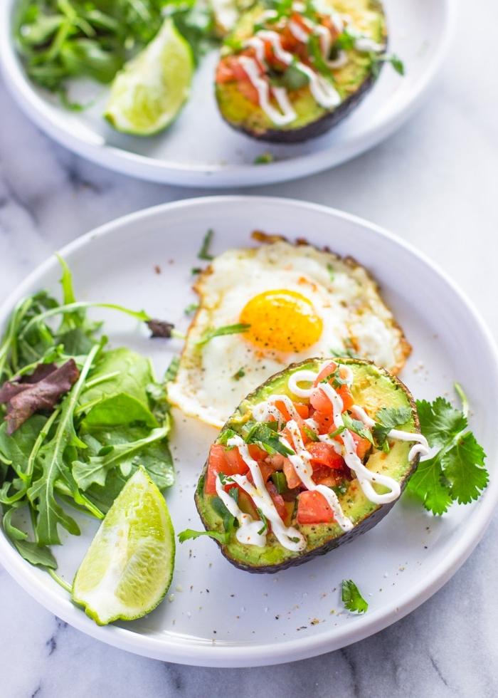 brunch ideen, gesunder frühstück, avocadohälfte gefüllt mit tomaten salza und garniert mit weißer soße, gebratenes ei, grüner salat