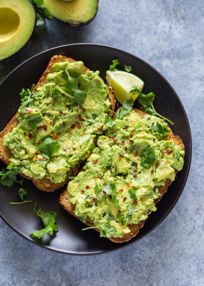 brunch ideen, toasts mit avocado und eiern garniert mit chilli und petersillie, gesund essen