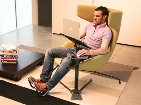 ein-mann-liegt-auf-einem-stuhl-und-arbeitet-am-laptop