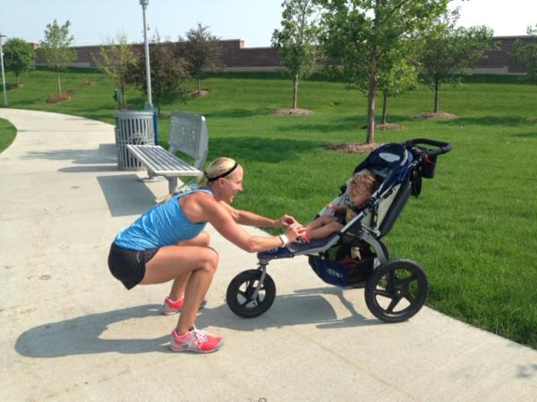 eine-coole-mutti-macht-sportliche-übungen-mit-dem-kinderwagen-im-park