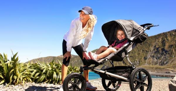 eine-schöne-blonde-mutter-mit-dem-kind-im-kinderwagen-macht-spaziergang