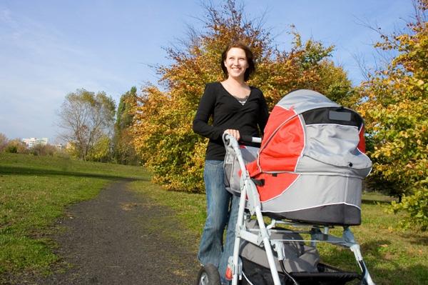 einfach-aussehende-frau-macht-spaziergang-in-der-reinen-natur-mit-einem-kinderwagen