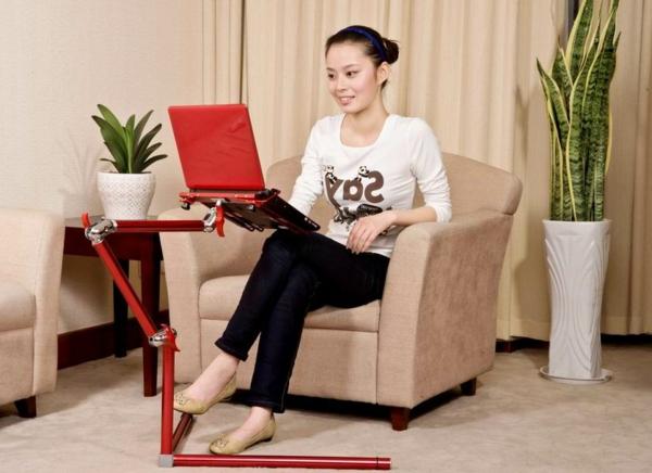 frau-sitzt-im-sessel-und-arbeitet-am-notebook-tisch-in-roter-farbe