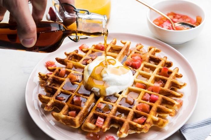 frühstücksbuffet selbst gemacht, waffeln mit vanille garniert mit honig, erdbeeren und sahne
