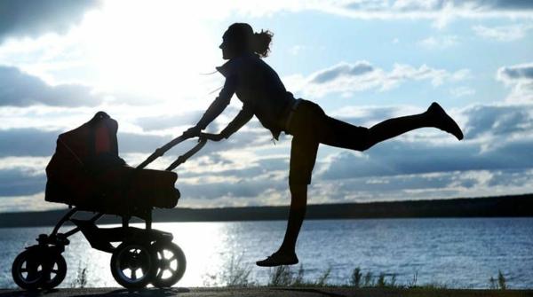 inspirierendes-foto-von-einer-mutter-mit-kinderwagen-sport-treiben-am-strand