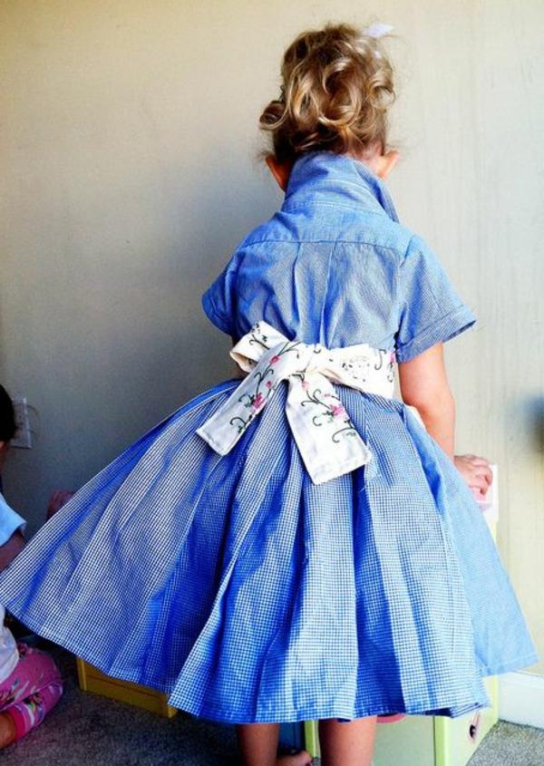kleines-mädchen-mit-einem-blauen-kleid-mit-weißer-schleife