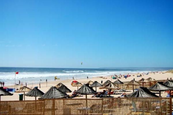 lissabon-strand-blauer-himmel-schöner-strand mit vielen sonnenschirmen