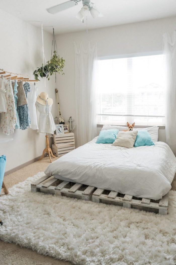 Schlafzimmer in Boho Look, Palettenbett mit weißer Bettwäsche, flauschiger Teppich