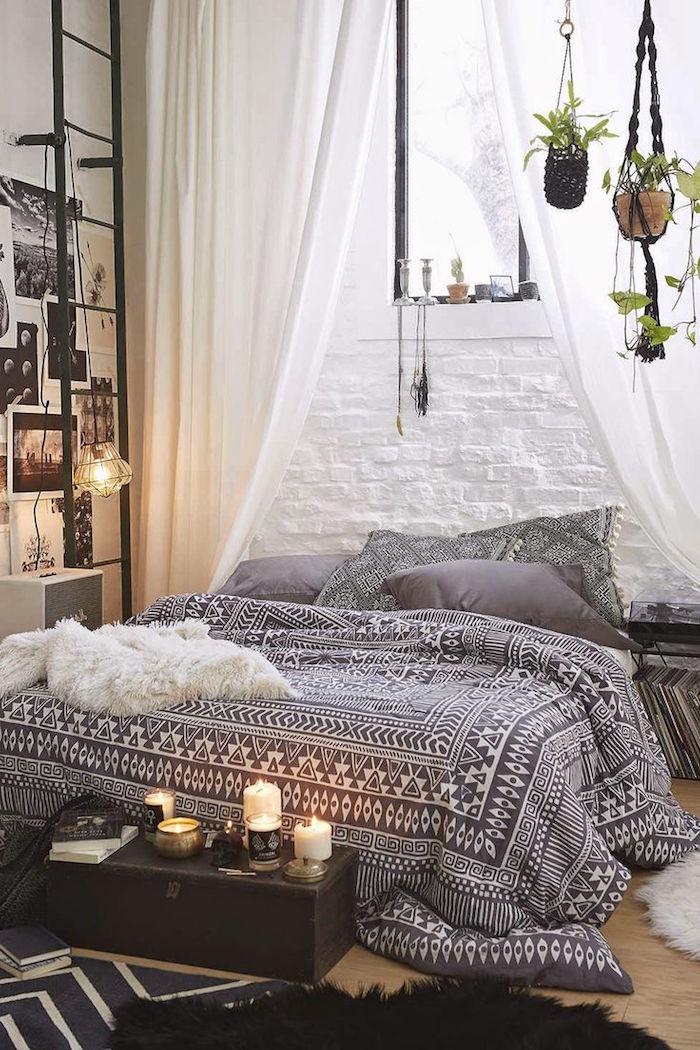 Boho Schlafzimmer, hängende Grünpflanzen, Kerzen und Fotos, schwarz weiße Bettwäsche