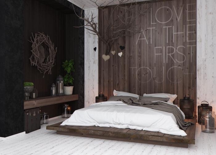 Landhaus Einrichtung im Schlafzimmer, Paletten Bett, weiße Bettwäsche, Holzwand und Boden