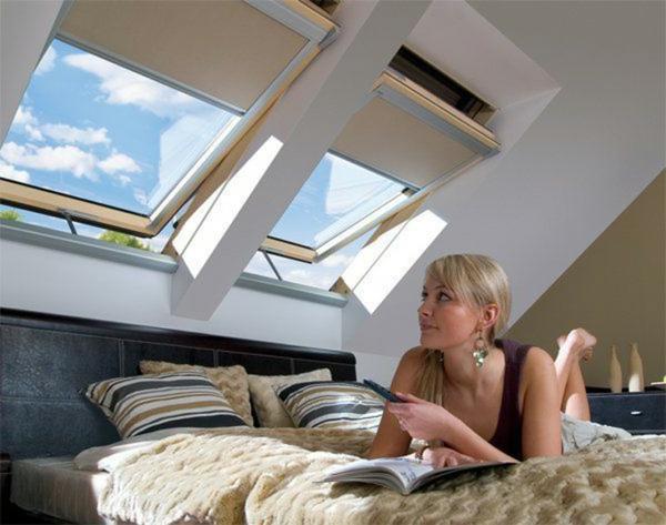 schlafzimmer-mit-dachschräge-eine-frau-liegt-auf-dem-bett