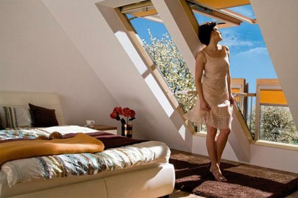 schlafzimmer-mit-dachschräge-eine-frau-steht-neben-den-fenstern