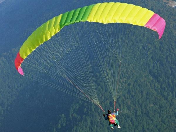 farbiger-Fallschirm-Fallschirmspringen-fliegen-Gebirge-Wald