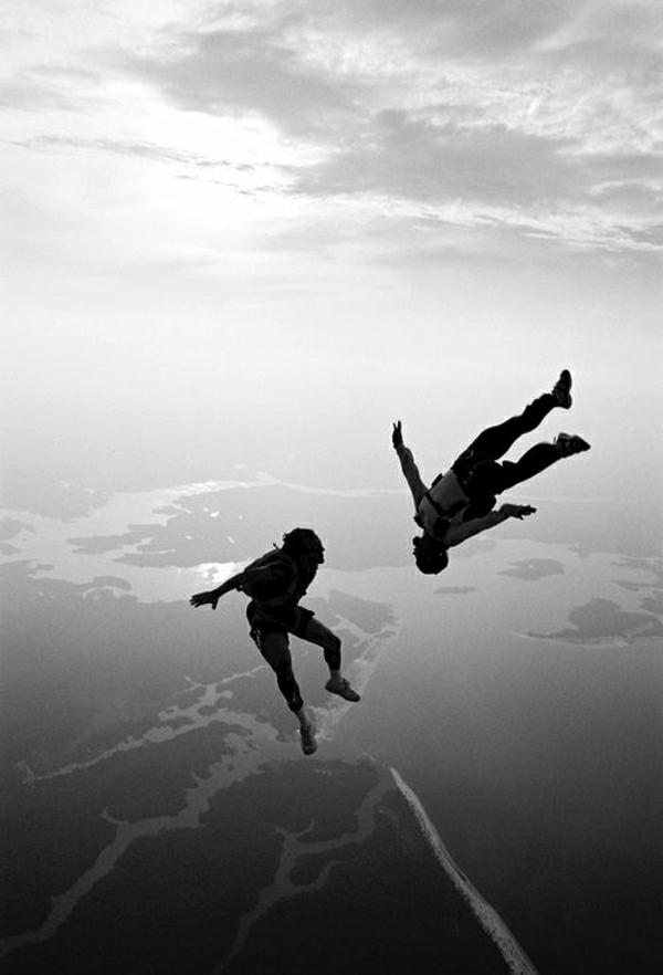 Fallschirm-Springen-zwei-Menschen-Himmel-Erde-Oberfläche-Wolken-schwarz-weiß