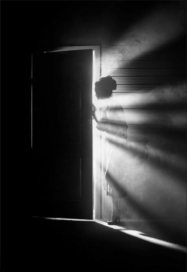 Frau-guckend-Tür-Sonnenstrahl