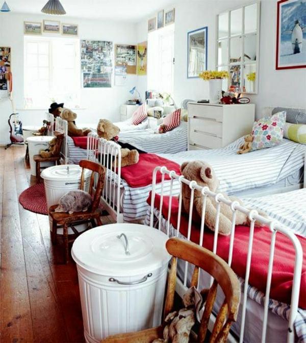 Kinderzimmer-vier-Eisenbette-Plüschenbären-weiße-Kommode-Fenster-Holzstühle