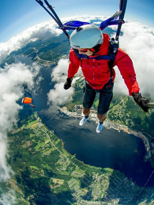 Paragleiten-Mann-Sportausrüstung-Helm-Wasser-Natur-Himmel-Wolken-rote-Jacke