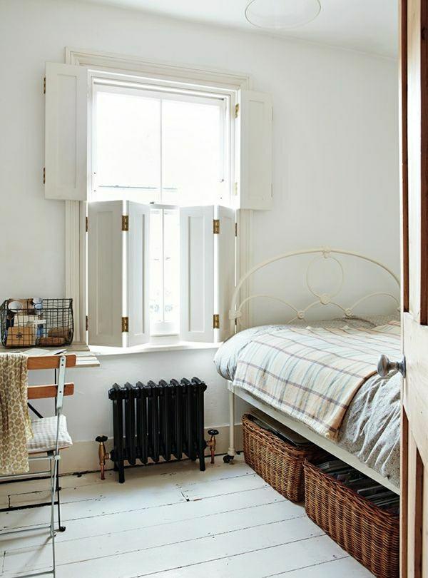 Schlafzimmer-Bett-Fensterläden-weiß-Weidenkörbe-unter-dem-Bett-Heizkörper