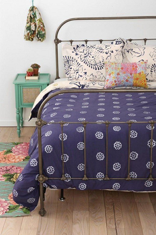 Schlafzimmer-Bett-lila-Bettzeug-Kissen-Blumentöpfe-Schal-mintgrüner-Nachttisch-Teppich-Blumen-Dekoration