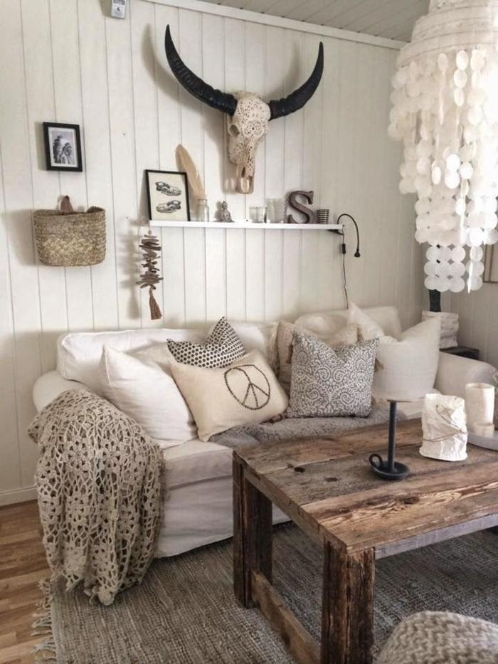 Schlafzimmer-in-Boho-Stil-Korb-Feder-Kerzen-Bilder-Kronleuchter-hölzerner-Tisch-Kissen