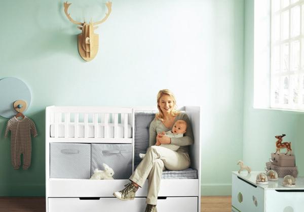 babyzimmer-mit-einem-funktionellen-babybett-mutti-sitzt-darauf- helle wandgestaltung