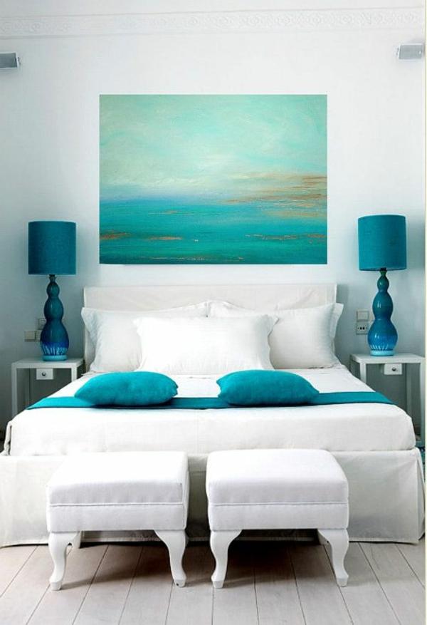dekoration-in-türkis-farbe-herrliches-bild-an-der-wand-im-weißes-schafzimmer-mit-dekorativen-kissen-auf-dem-bett