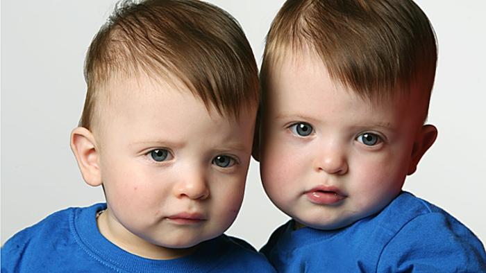eineiige-zwillinge-kleine-süße-jungen-mit-blauer-kleidung