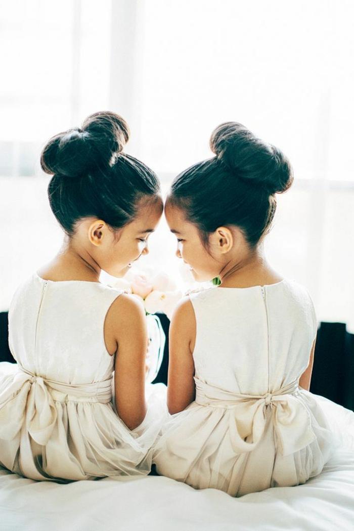 eineiige-zwillinge-mit-eleganten-frisuren-und-weißen-kleidern