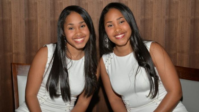 eineiige-zwillinge-zwei-junge-frauen-mit-langen-schwarzen-haaren-und-weißen-kleidern