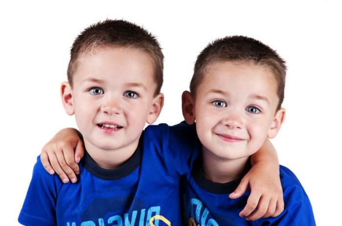 eineiige-zwillinge-zwei-lächelnde-jungen-mit-blauer-kleidung