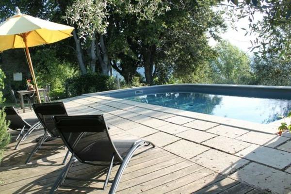 ferienhaus-in-toskana-mit-pool-gelber-sonnenschirm ganz neben dem pool