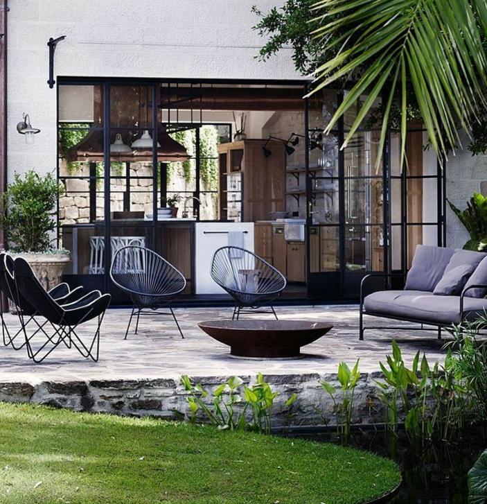 feuerstelle-für-terrasse-gläserne-wände-grünes-gras