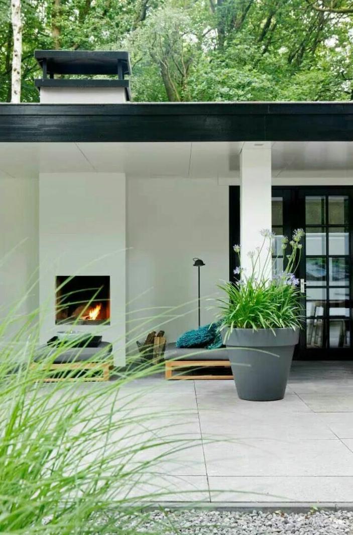 feuerstelle-für-terrasse-weiße-säule-grüne-pflanzen