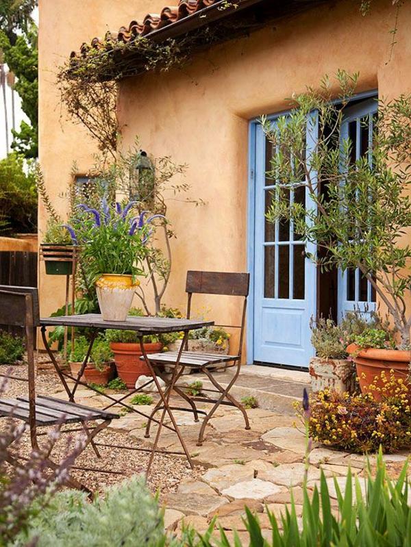 gartenhaus-mit-terrasse-blaue-tür-und-grüne-pflanzen