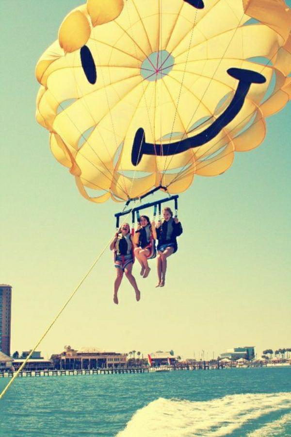 gelber-Fallschirm-Lächeln-Para-Sailing-drei-Mädchen-Strand-Meer