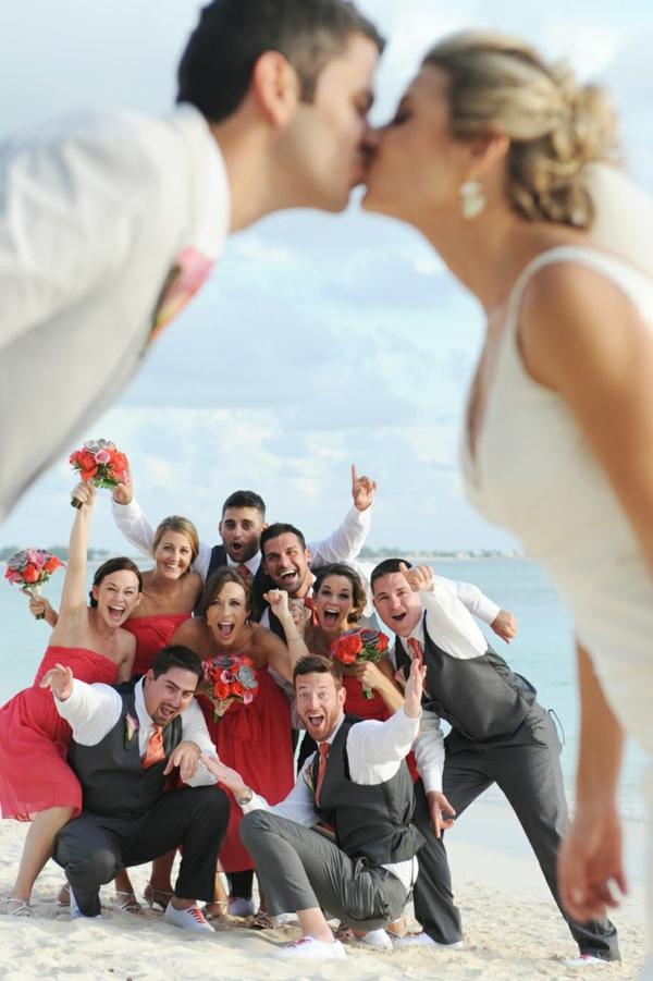 heiraten-am-strand-braut-und-bräutigam-küssen-sich-vor-ihren-freunden