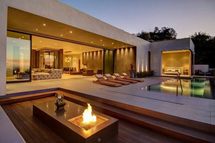 Elegante offene feuerstelle auf einer großen terrasse mit pool
