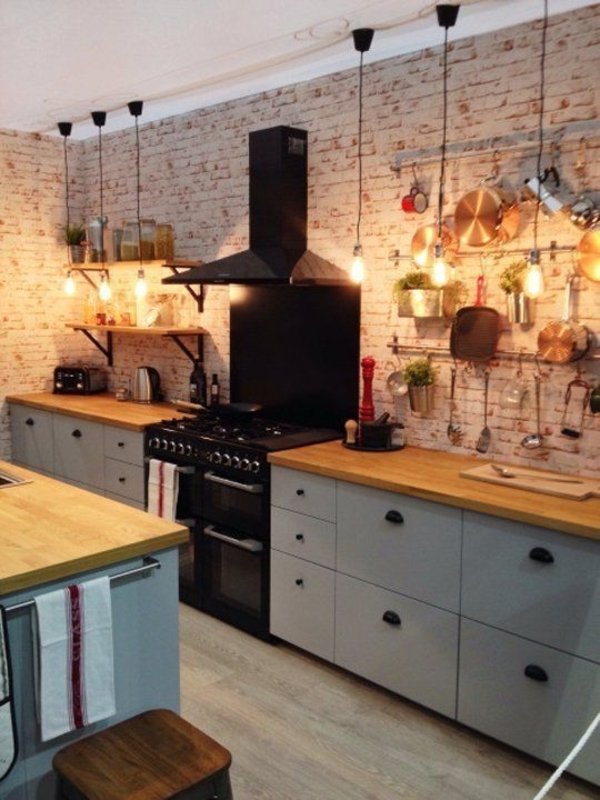 rustikale-Küche-Ziegenwände-hängende-Leuchten-schwarzer-Herd