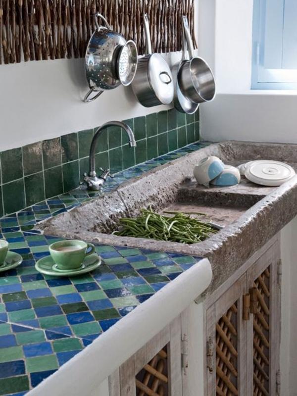 rustikale-Sommerhütte-in-Portugalien-Mosaik-Steingut-Waschbecken-aus-Stein-Gemüse-Kaffeetassen-Pfannen
