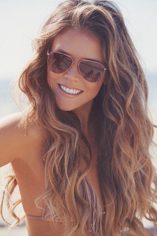 lächelnde frau mit sonnenbrillen und langen haaren am strand