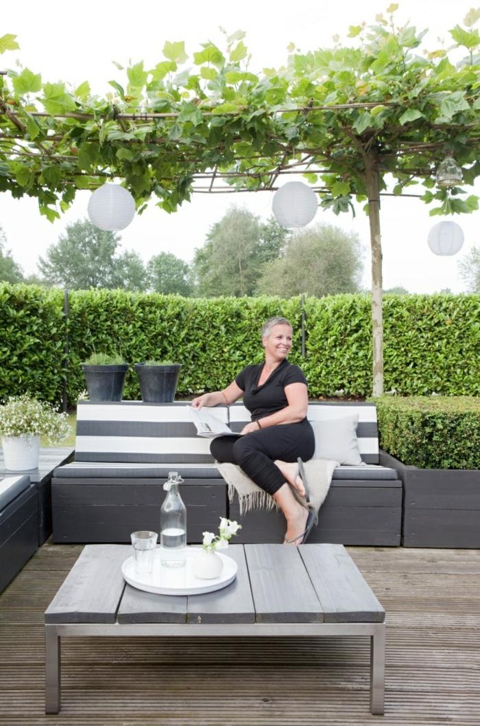 terrassenüberdachunggrüne-pflanzen-und-tisch-mit-sofa