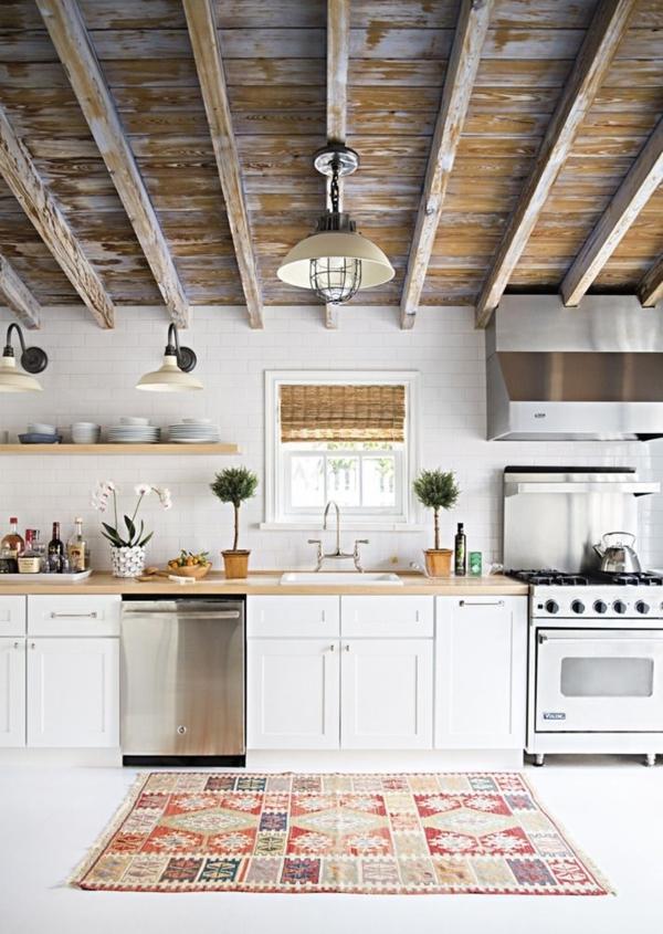 weiße-hölzerne-Landhausküche-industriale-Leuchten-Küchenschränke-Blumentöpfe-Teppich