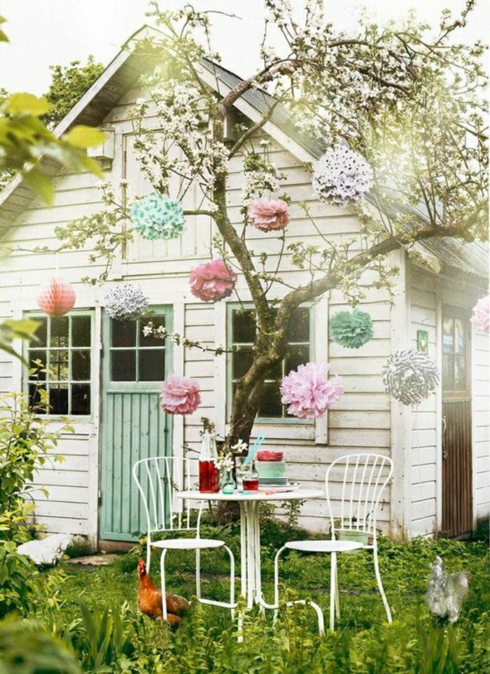 weißes-Gartenhäuschen-Gras-Tisch-Stühle-Baum-Papierblumen-Huhn