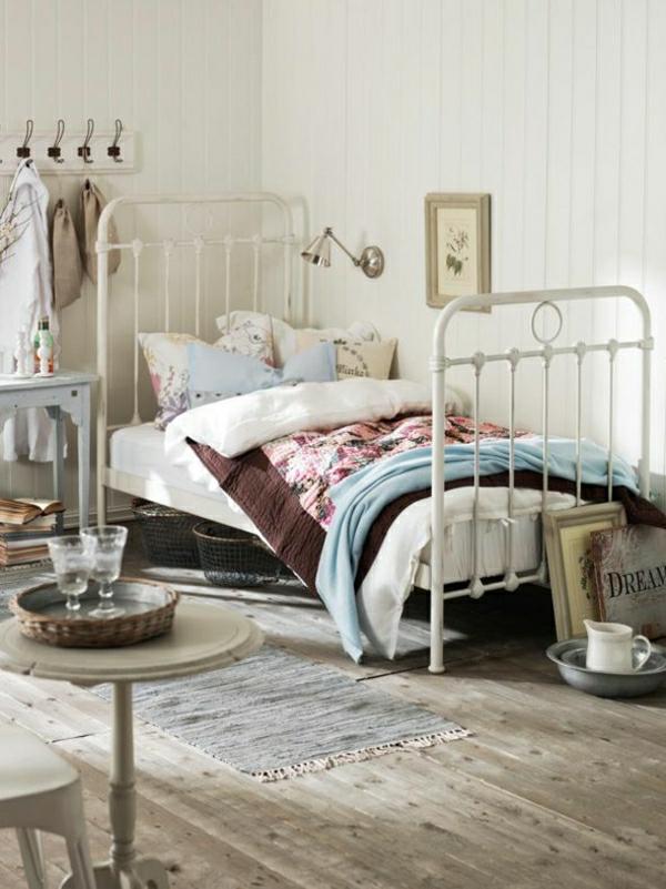 weißes-Bett-Kissen-Tisch-Kanne-Gläser-Bilder-Kleiderablage