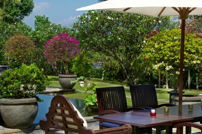 mediterrane-Gartengestaltung--Stil-Blumentöpfe-Sträuche-hölzerne-Möbel